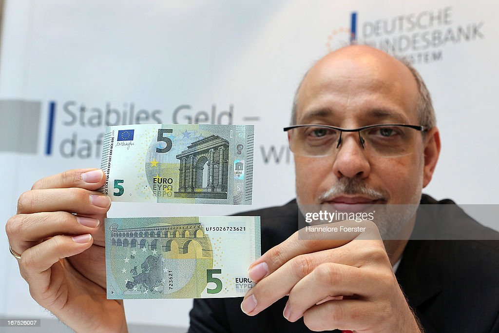 Stefan Hardt, President of the Regional Office displays the new 5 Euro note of the German Bundesbank during a demonstration for the media on April 26, 2013 in Mainz, Germany. The center is Germany's main facility for analysing potentially counterfeit money and also repairs damaged banknotes.