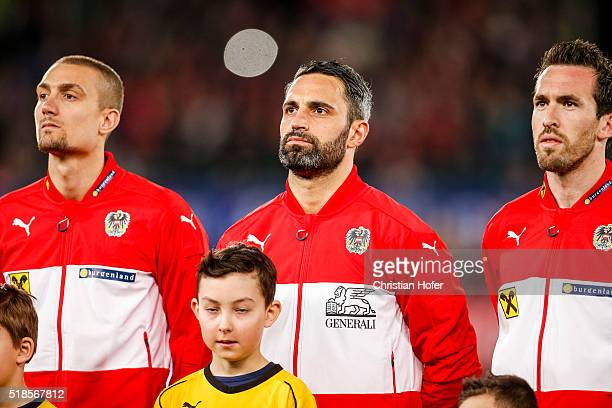 Stefan Ilsanker goalkeeper Ramazan Oezcan and Christian Fuchs of Austria line up during the national anthem prior to the international friendly match...