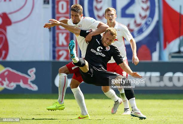 Stefan Ilsanker of Leipzig challenges Lennart Thy of St Pauli during the Second League match between RB Leipzig and FC StPauli at RedBull Arena on...