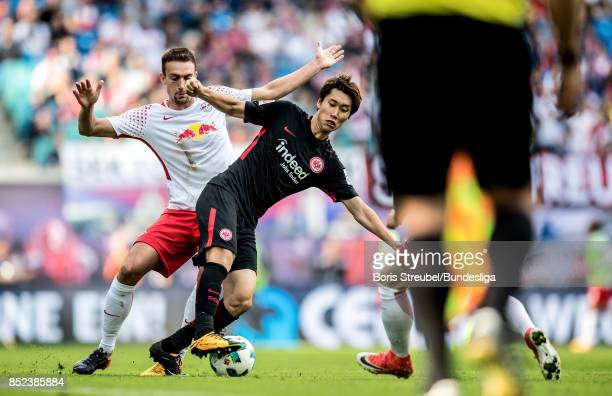 Stefan Ilsanker of RB Leipzig in action with Daichi Kamada of Eintracht Frankfurt during the Bundesliga match between RB Leipzig and Eintracht...