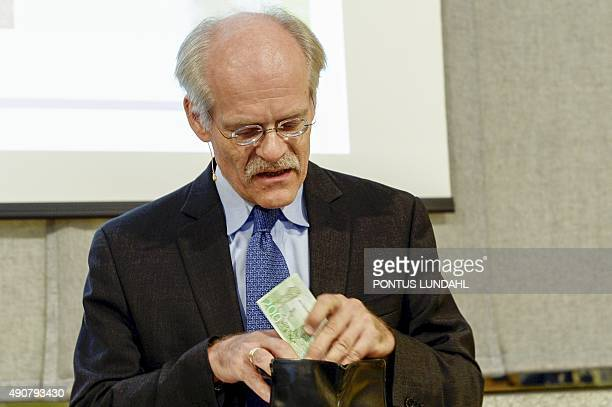 Stefan Ingves the head of Sweden's central bank the Riksbank pulls a new 200 kronor bank note from his wallet at a press conference in Stockholm on...
