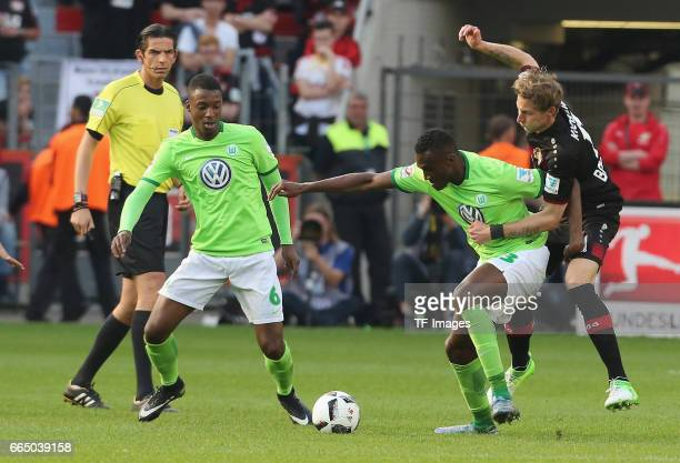 Stefan Kiessling lecr and Josuha Guilavoqui of Wolfsburg and Riechedly Bazoer battle for the ball during the Bundesliga match between Bayer 04...