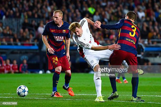 Stefan Kiessling of Bayer 04 Leverkusen competes for the ball with Jeremy Mathieu and Gerard Pique of FC Barcelona during the UEFA Champions League...