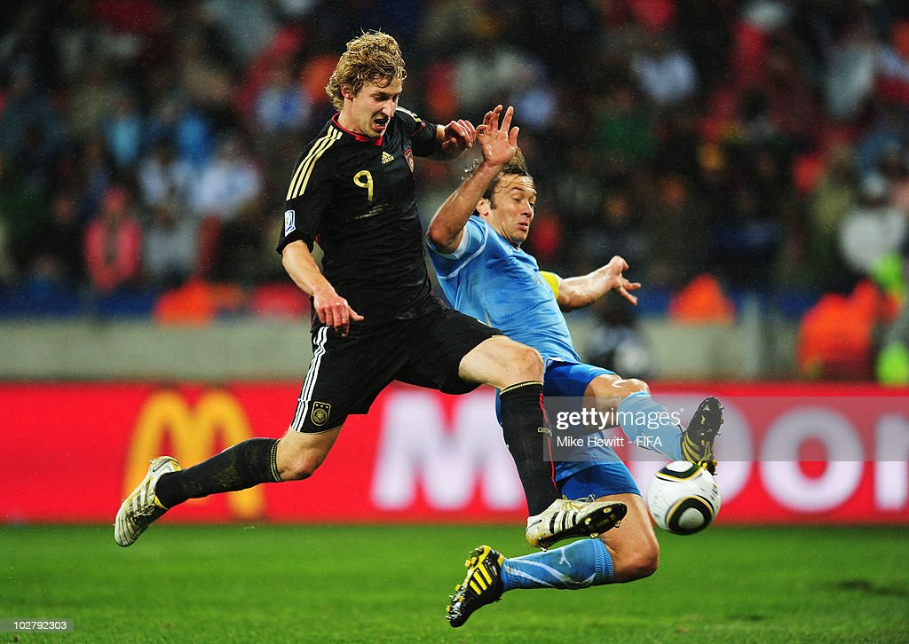 Stefan Kiessling of Germany is tackled by Diego Lugano of Uruguay during the 2010 FIFA World Cup South Africa Third Place Playoff match between...