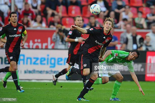 Stefan Kiessling of Leverkusen and Makoto Hasebe of Wolfsburg battle for the ball during the Bundesliga match between Bayer 04 Leverkusen and VfL...