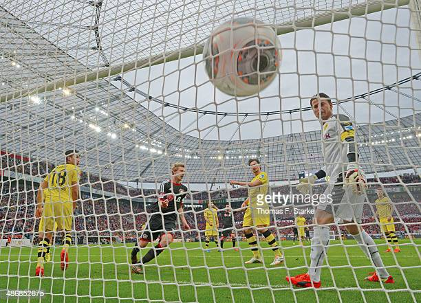 Stefan Kiessling of Leverkusen celebrates his teams first goal while Nuri Sahin Mats Hummels and goalkeeper Roman Weidenfeller of Dortmund look...