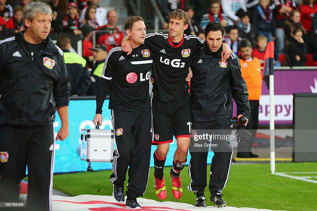 Stefan Kiessling of Leverkusen is led off the pitch during the Bundesliga match between Bayer Leverkusen and FC Bayern Muenchen at BayArena on October 5, 2013 in Leverkusen, Germany.