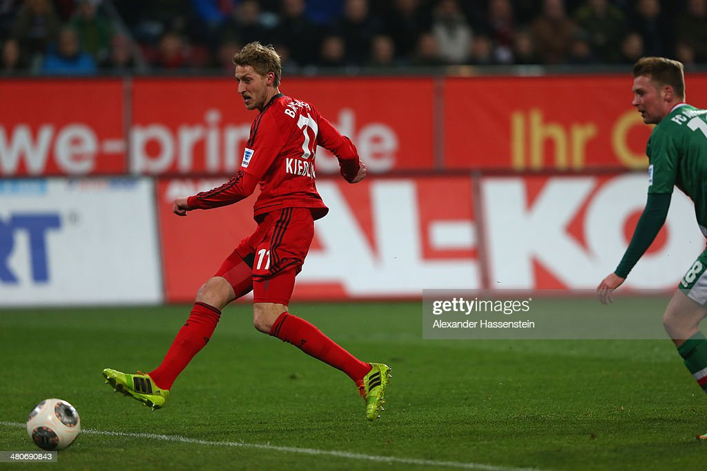 Stefan Kiessling of Leverkusen scores the opening goal against JanIngwer CallsenBracker of Augsburg during the Bundesliga match between FC Augsburg...