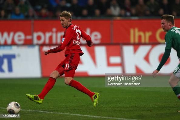 Stefan Kiessling of Leverkusen scores the opening goal against JanIngwer CallsenBracker of Augsburg during the Bundesliga match between FC Augsburg...