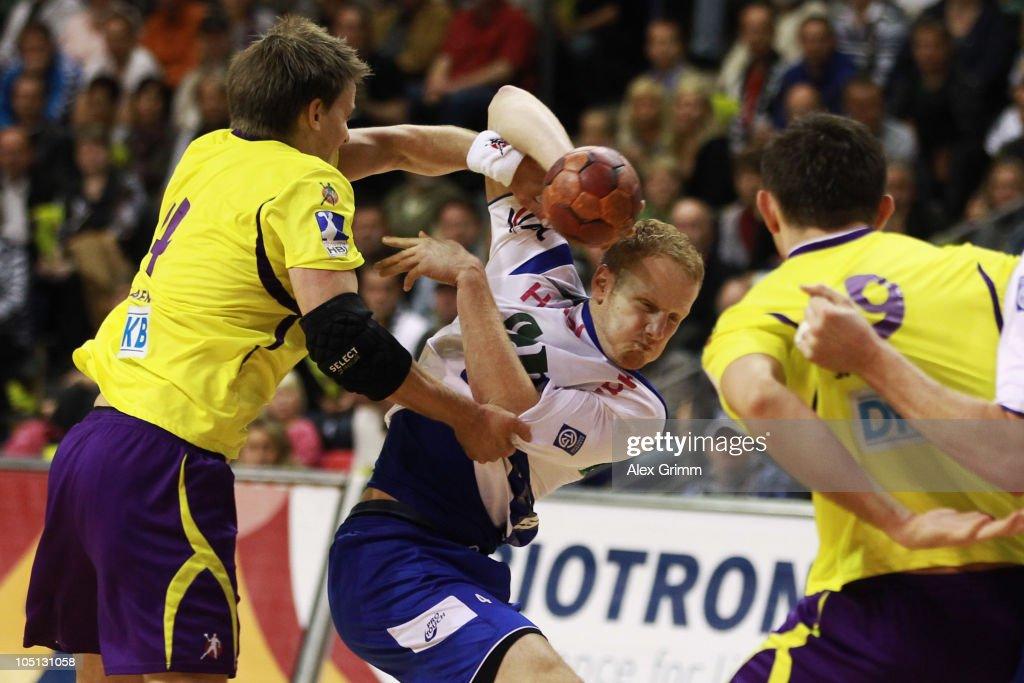 Stefan Kneer (C) of Grosswallstadt is challenged by Torsten Laen of Berlin during the Toyota handball Bundesliga match between Fuechse Berlin and TV Grosswallstadt at the Max-Schmeling-Halle on October 10, 2010 in Berlin, Germany.