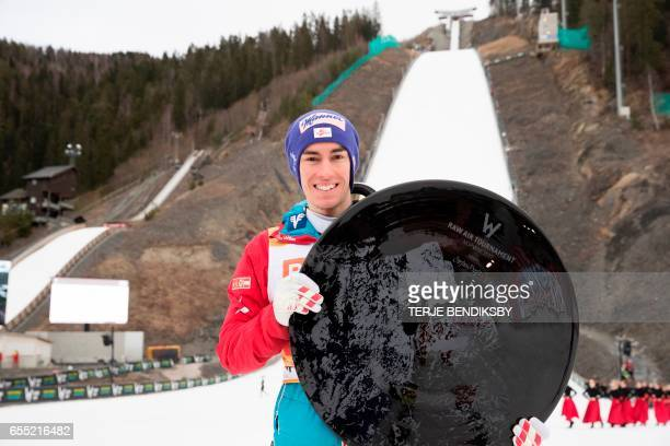 Stefan Kraft from Austria holds the trophy for overall victory in the RAW AIR ski jumping tournament after the final competition in Vikersund 19...