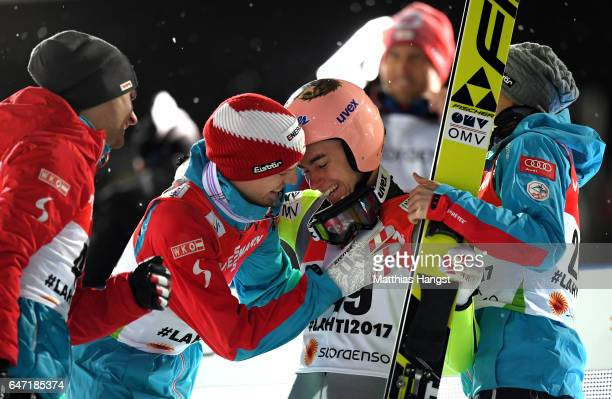 Stefan Kraft of Austria is congratulated by Michael Hayboeck of Austria and Manuel Fettner of Austria as he wins gold during the Men's Ski Jumping...