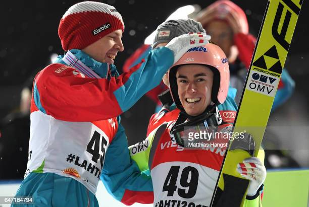 Stefan Kraft of Austria is congratulated by Michael Hayboeck of Austria as he wins gold during the Men's Ski Jumping HS130 at the FIS Nordic World...