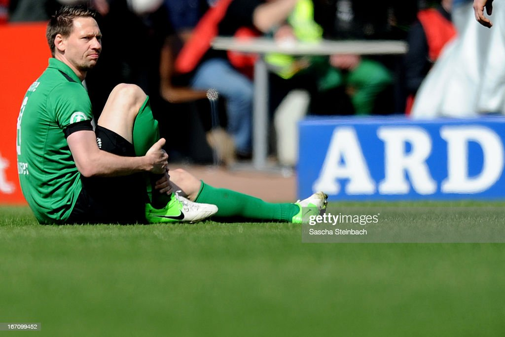 Stefan Kuehne (C) of Muenster sits on the pitch after picking up an injury during the 3. Liga match between Preussen Muenster and Karlsruher SC at Preussenstadion on April 20, 2013 in Muenster, Germany.