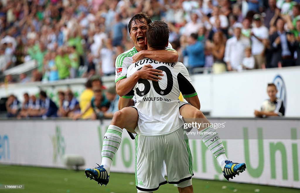 Stefan Kutschke of Wolfsburg celebrates with team-mate <a gi-track='captionPersonalityLinkClicked' href=/galleries/search?phrase=Marcel+Schaefer&family=editorial&specificpeople=656515 ng-click='$event.stopPropagation()'>Marcel Schaefer</a> after scoring their fourth goal during the Bundesliga match between VfL Wolfsburg and FC Schalke 04 at Volkswagen Arena on August 17, 2013 in Wolfsburg, Germany.
