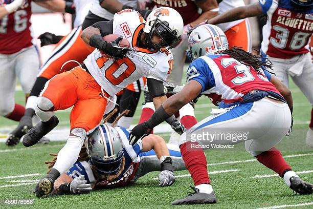 Stefan Logan of the BC Lions runs with the ball in from of Bear Woods and Jerald Brown of the Montreal Alouettes during the CFL Eastern Division...