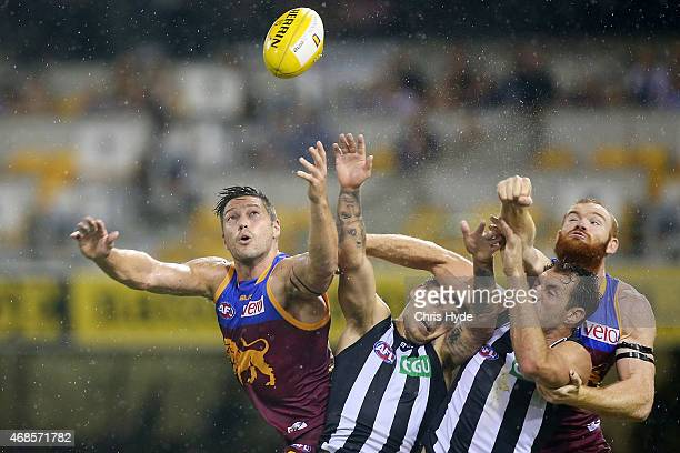 Stefan Martin and Daniel Merrett of the Lions and Jamie Elliott and Travis Cloke of the Magpies contest a mark during the round one AFL match between...