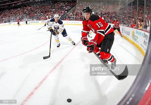 Stefan Matteau of the New Jersey Devils in action against Kevin Porter of the Buffalo Sabres at the Prudential Center on March 7 2013 in Newark New...
