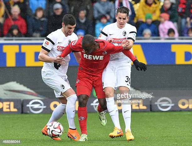 Stefan Mitrovic and Christian Guenter of SC Freiburg challenge Anthony Uhja of 1 FC Koeln during the Bundesliga match between Sport Club Freiburg and...