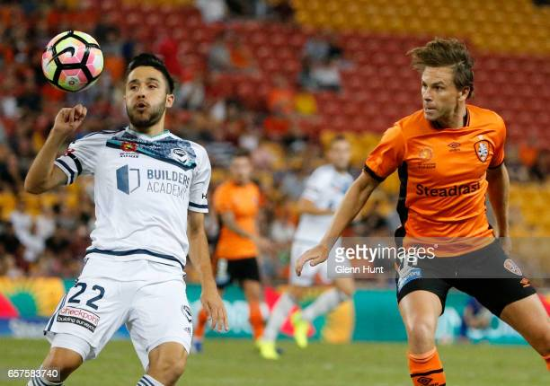 Stefan Nigro of the Victory controls the ball while Brett Holman of the Roar watches on during the round 24 ALeague match between Brisbane Roar and...