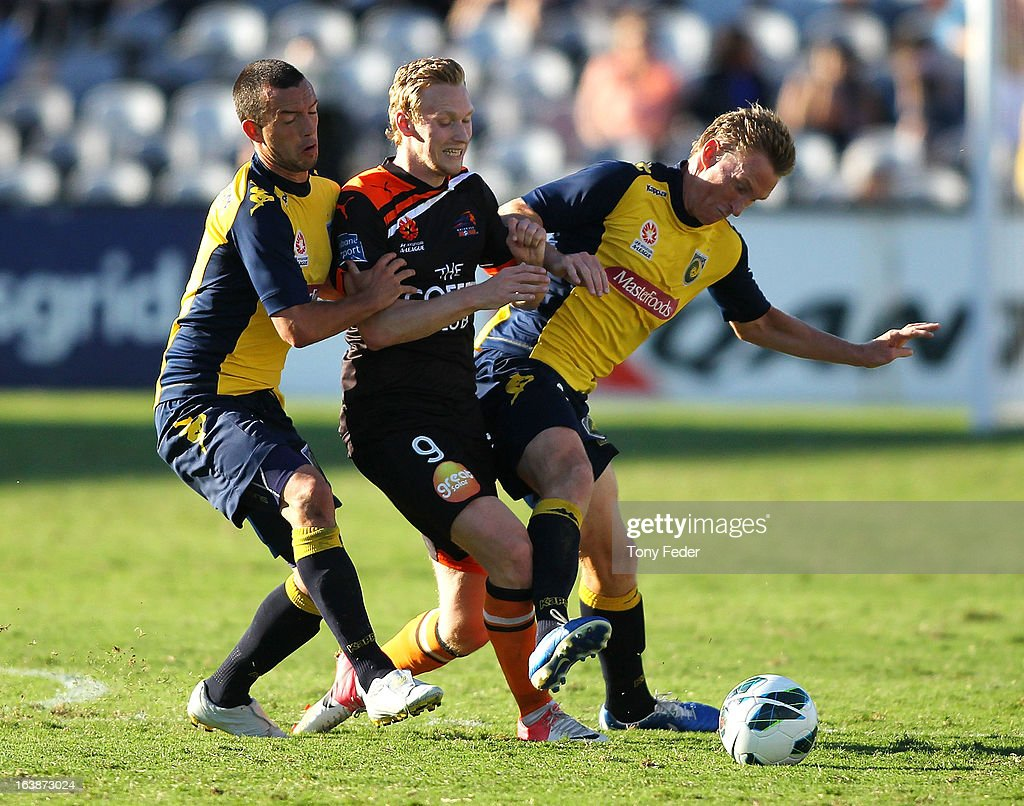 Stefan Nijland of Brisbane Roar is caught between John Hutchinson and <a gi-track='captionPersonalityLinkClicked' href=/galleries/search?phrase=Daniel+McBreen&family=editorial&specificpeople=2229191 ng-click='$event.stopPropagation()'>Daniel McBreen</a> of the Mariners during the round 25 A-League match between the Central Coast Mariners and the Brisbane Roar at Bluetongue Stadium on March 17, 2013 in Gosford, Australia.
