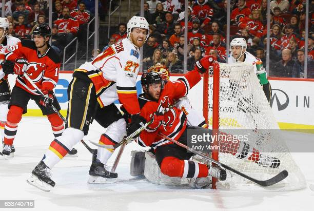 Stefan Noesen of the New Jersey Devils is knocked into the net by Dougie Hamilton of the Calgary Flames during the game at Prudential Center on...