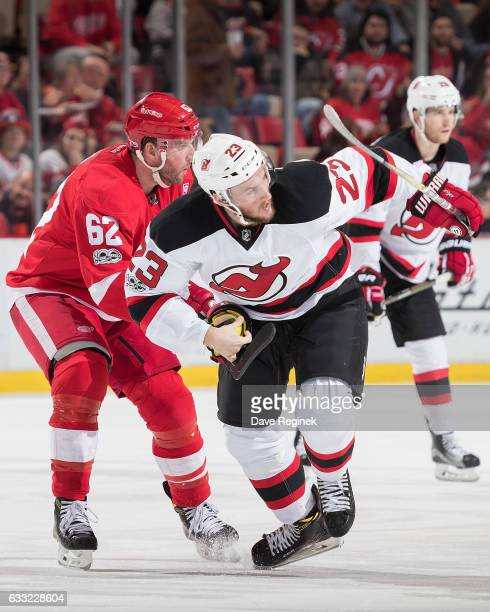Stefan Noesen of the New Jersey Devils skates up ice followed by Thomas Vanek of the Detroit Red Wings during an NHL game at Joe Louis Arena on...