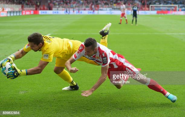 Stefan Ortega of Arminia Bielefeld and Steven Skrzybski of 1 FC Union Berlin during the game between Union Berlin and Arminia Bilefeld on august 27...