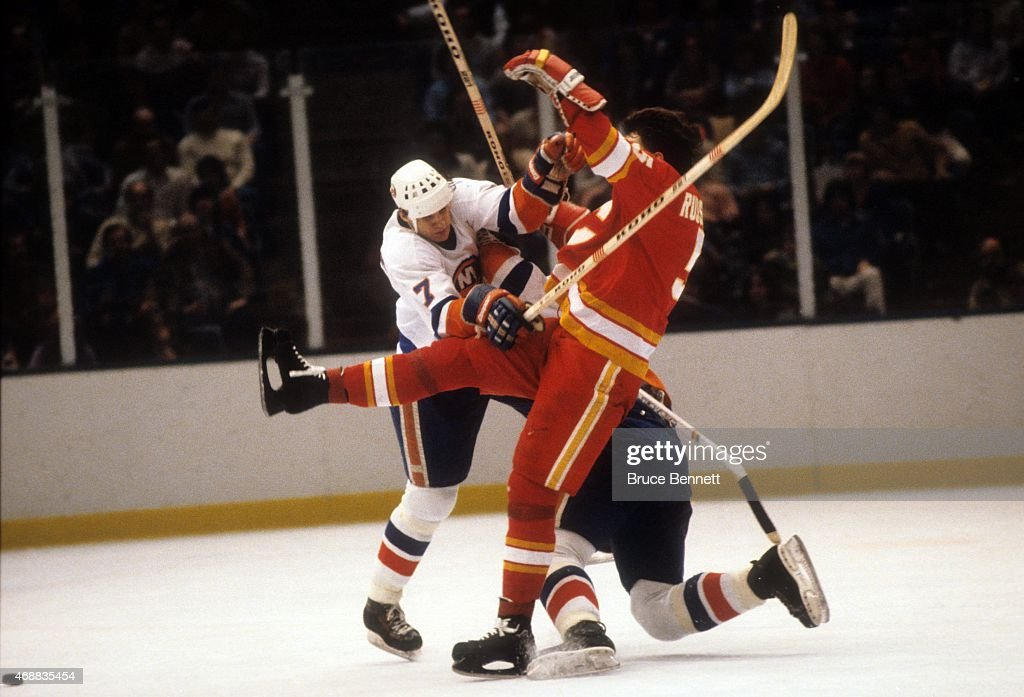 Stefan Persson of the New York Islanders checks Phil Russell of the Calgary Flames during their game circa 1980 at the Nassau Coliseum in Uniondale...