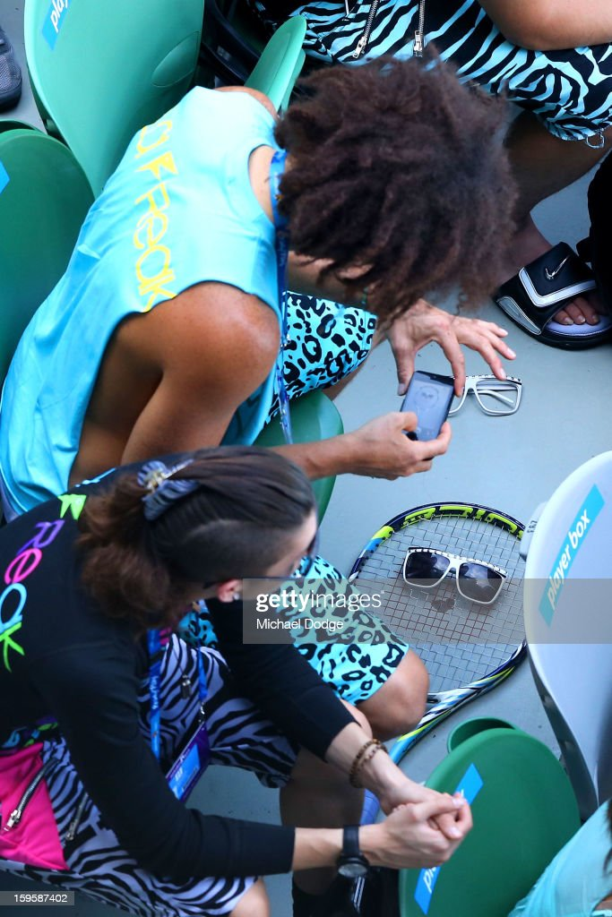 Stefan 'Redfoo' Gordy of the American electro duo LMFAO takes a photo on his phone at the women's first round match between Victoria Azarenka of Belarus and Eleni Daniilidou of Greece during day four of the 2013 Australian Open at Melbourne Park on January 17, 2013 in Melbourne, Australia.