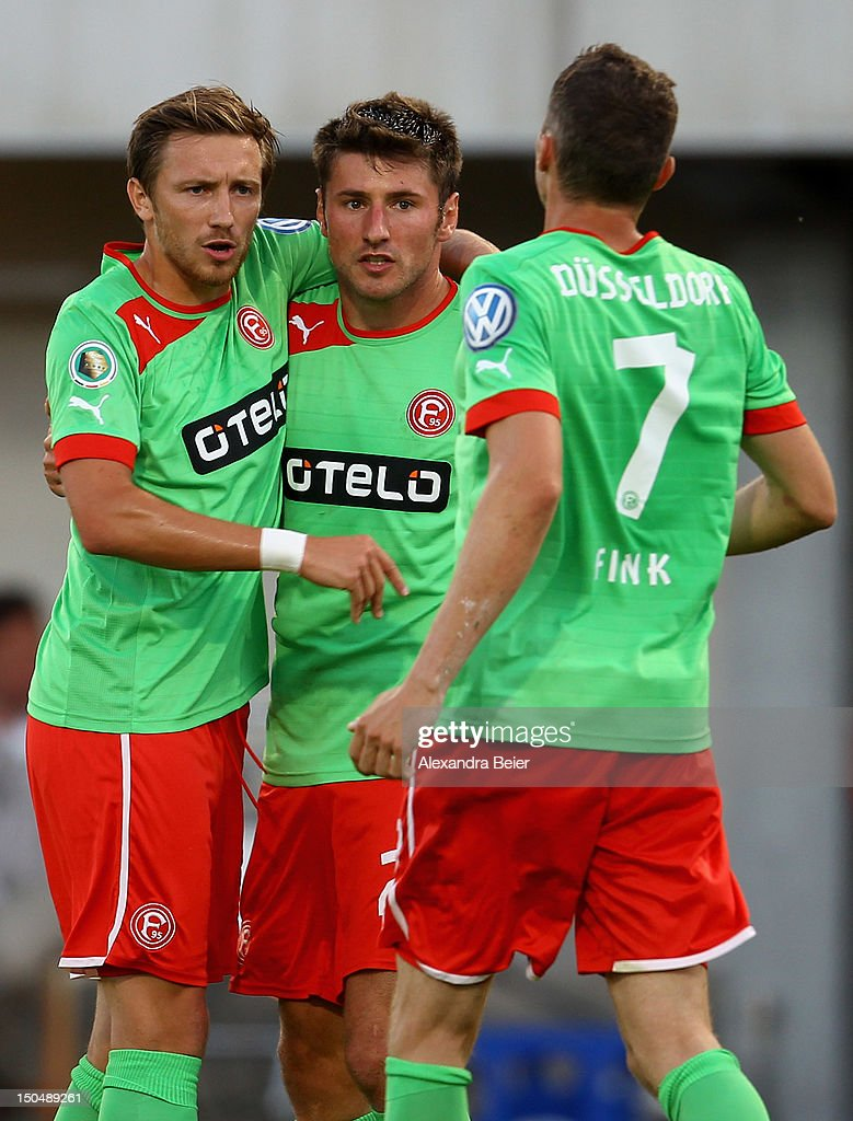 Stefan Reisinger of Duesseldorf celebrates with his teammates Andriy Voronin and Oliver Fink after scoring their first goal during the DFB Cup first...