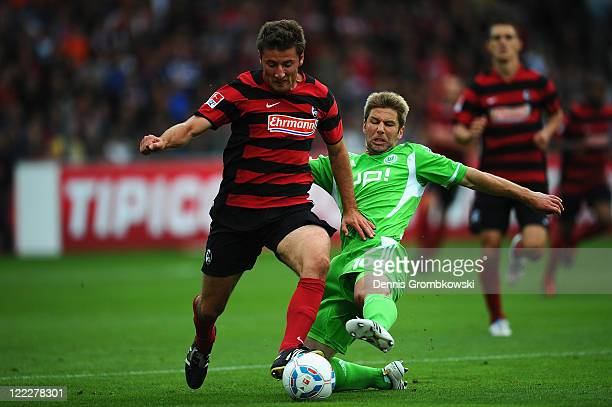 Stefan Reisinger of Freiburg is challenged by Thomas Hitzlsperger of Wolfsburg during the Bundesliga match between SC Freiburg and VfL Wolfsburg at...