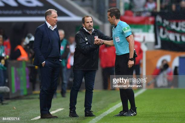 Stefan Reuter manager of Augsburg and head coach Manuel Baum talk to referee Tobias Stieler during the Bundesliga match between FC Augsburg and 1 FC...