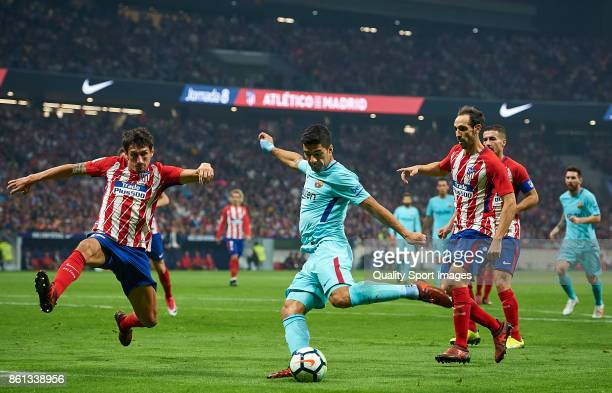 Stefan Savic and Juanfran of Atletico Madrid competes for the ball with Luis Suarez of Barcelona during the La Liga match between Atletico Madrid and...