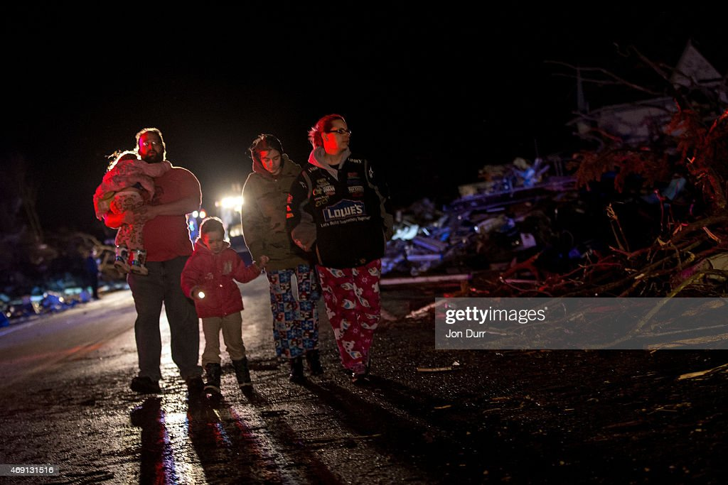 Stefanie and Matthew Hurley look at the wreckage on the IL72 with their family after a tornado came through the town earlier in the day on April 9...