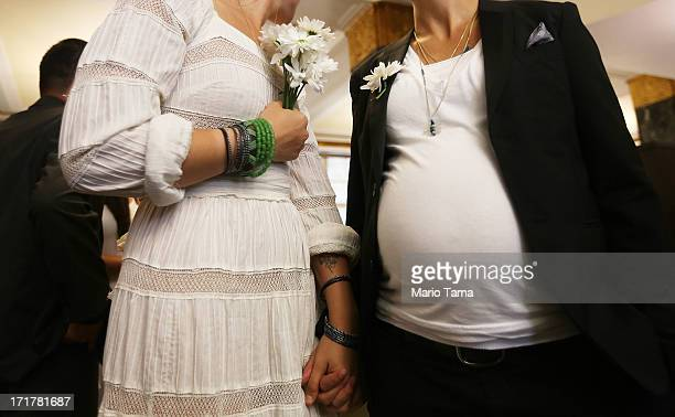 Stefanie Berks and Daisy Boyd hold hands by Boyd's pregnant belly before their marriage ceremony at the Manhattan Marriage Bureau two days after the...