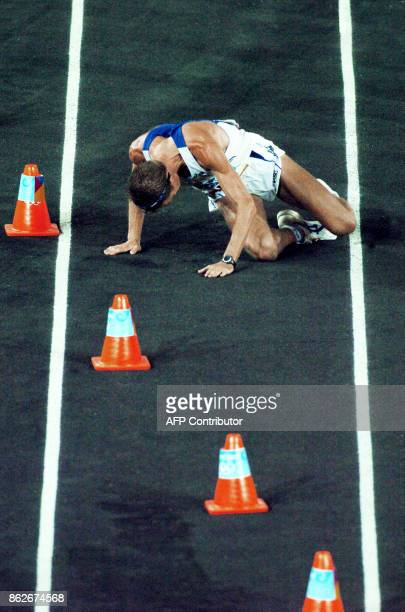 Stefano Baldini of Italy collapses after crossing the finish line to win the Olympic Games men's marathon 29 August 2004 at the Panathinaiko Stadium...