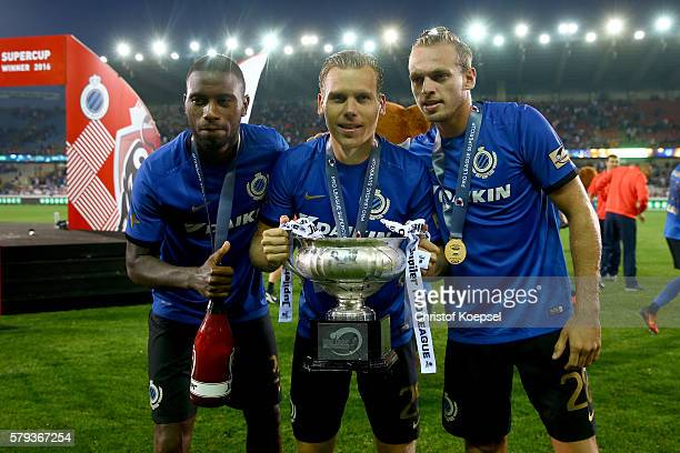 Stefano Denswill Ruud Vormervand Laurens de Bock of Brugge pose with the trophy after winning 21 the Supercup match between Club Brugge and Standrad...