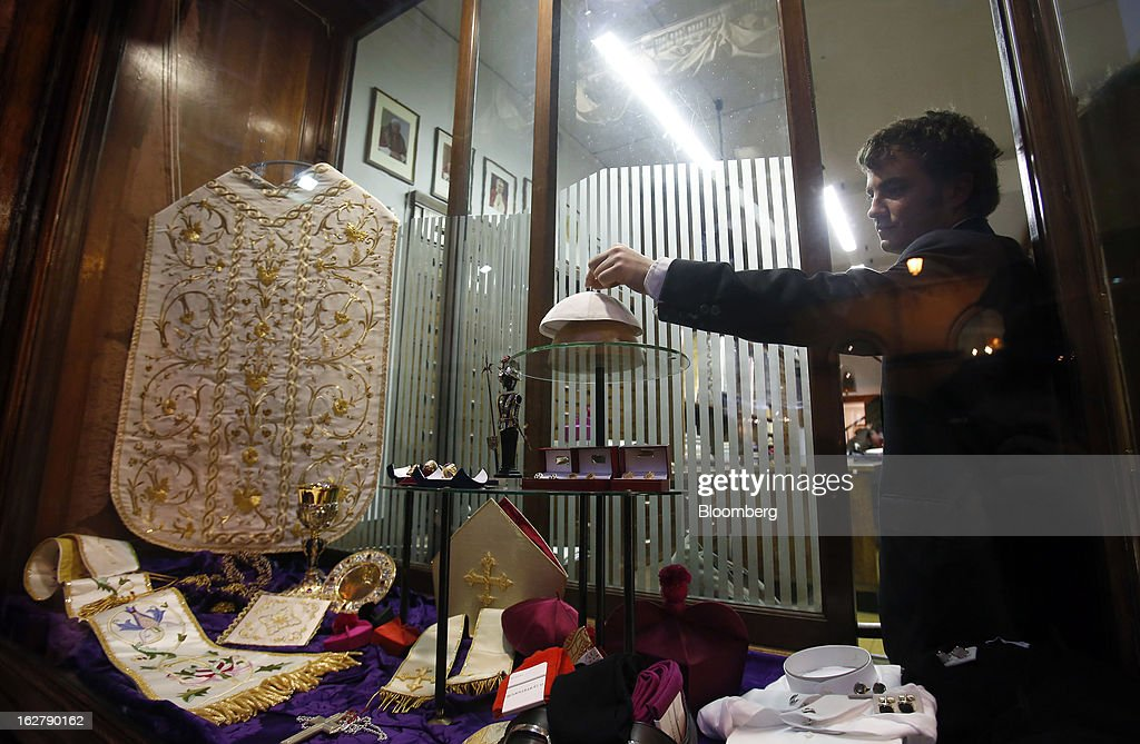 Stefano Gammarelli, an ecclesiastical tailor at Gammarelli, arranges a white papal skull cap in the window display of his family's store in Rome, Italy, on Friday, Feb. 22, 2013. Gammarelli was founded in 1797 under Pope Pius VI as tailors to the clergy, and lists other papal customers as John Paul I, Paul VI, and John XXIII. Photographer: Alessia Pierdomenico/Bloomberg via Getty Images