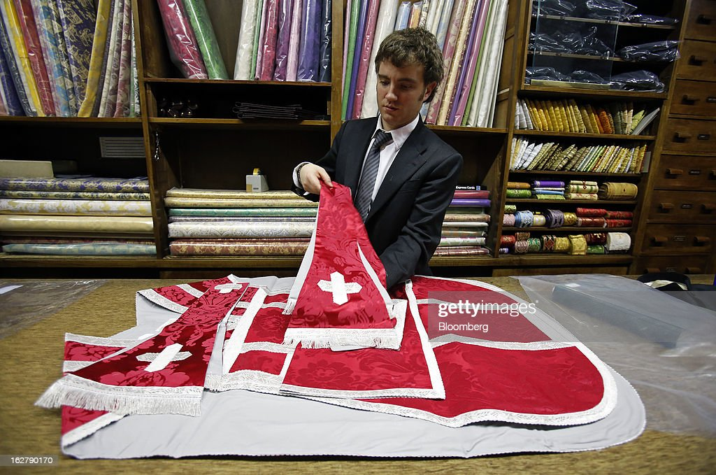 Stefano Gammarelli, an ecclesiastical tailor at Gammarelli, arranges a clerical chasuble as he works at the counter inside his family's store in Rome, Italy, on Friday, Feb. 22, 2013. Gammarelli was founded in 1797 under Pope Pius VI as tailors to the clergy, and lists other papal customers as John Paul I, Paul VI, and John XXIII. Photographer: Alessia Pierdomenico/Bloomberg via Getty Images