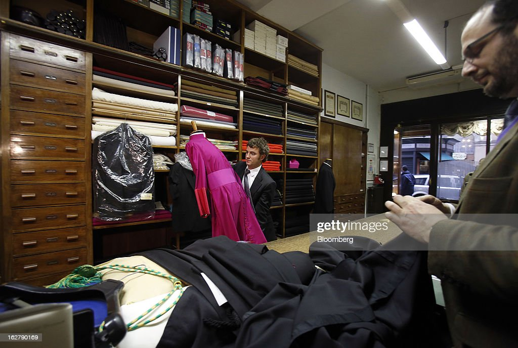 Stefano Gammarelli, an ecclesiastical tailor at Gammarelli, left, carries a mannequin dressed in a clerical outfit through his family's store in Rome, Italy, on Friday, Feb. 22, 2013. Gammarelli was founded in 1797 under Pope Pius VI as tailors to the clergy, and lists other papal customers as John Paul I, Paul VI, and John XXIII. Photographer: Alessia Pierdomenico/Bloomberg via Getty Images