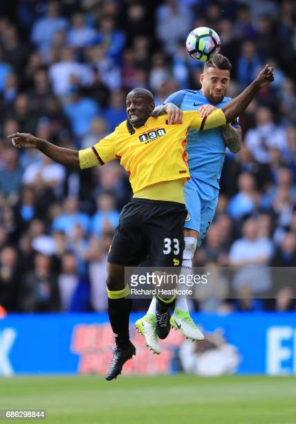 Stefano Okaka of Watford and Nicolas Otamendi of Manchester City clash during the Premier League match between Watford and Manchester City at...