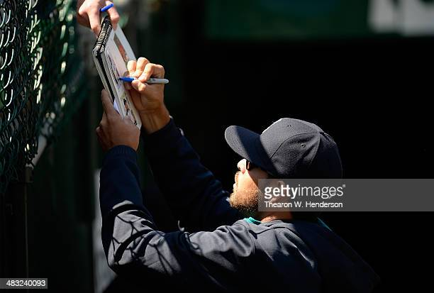 Stefen Romero of the Seattle Mariners signs an autograph for a fan prior to the start of his game against the Oakland Athletics at Oco Coliseum on...