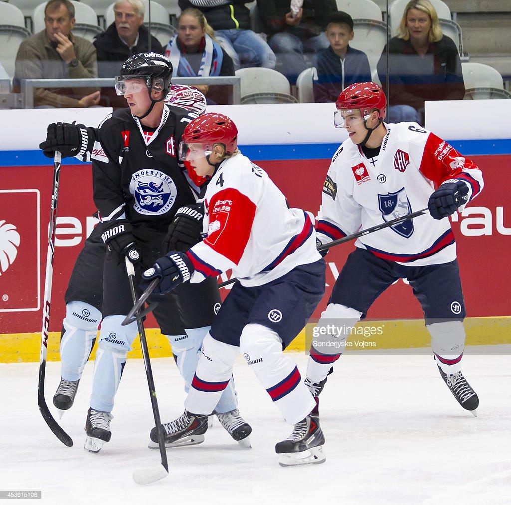 Steffen Frank of Sonderjyske Vojens battles with Juha Tarkanen (4) and Eemeli Heikkinen (6) of IFK Helsinki during the Champions Hockey League group stage game between Sonderjyske Vojens and IFK Helsinki on August 21, 2014 in Vojens, Denmark.