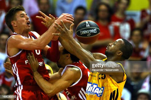 Steffen Hamann of Muenchen and his team mate Demond Green shoots against Je`Kel Foster of Berlin during Game 1 of the quarterfinals of the Beko...