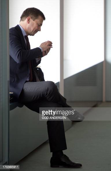 Steffen Seibert spokesman of German Chancellor Angela Merkel uses his mobile phone prior to the weekly cabinet meeting at the Chancellery in Berlin...