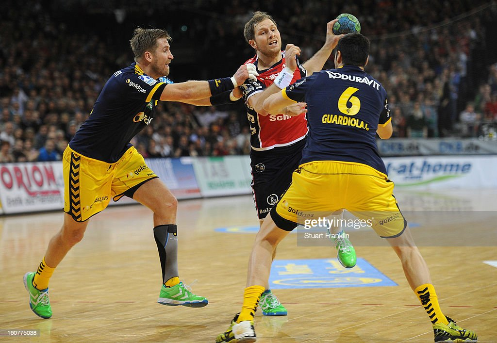 Steffen Weinhold of Flensburg challenges for the ball with <a gi-track='captionPersonalityLinkClicked' href=/galleries/search?phrase=Oliver+Roggisch&family=editorial&specificpeople=577212 ng-click='$event.stopPropagation()'>Oliver Roggisch</a> of Rhein-Neckar during the DHB cup game between SG Flensburg Handewitt and Rhein-Neckar Loewen at the Flens Arena on February 5, 2013 in Flensburg, Germany.