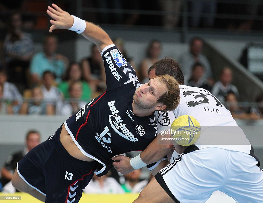 Steffen Weinhold of Flensburg is challenged by Ilic Momir (R) of Kiel during the Handball Supercup match between THW Kiel and SG Flensburg Handewitt at Olympia Eishalle on August 21, 2012 in Munich, Germany.