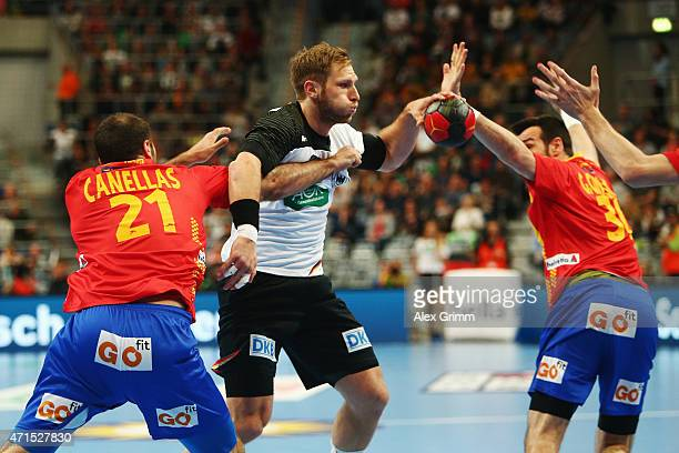 Steffen Weinhold of Germany is challenged by Joan Canellas Reixach and Gedeon Guardiola Villaplana of Spain during the European Handball Championship...