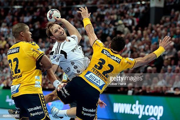 Steffen Weinhold of Kiel challenges for the ball with Alexander Petersson of Rhein Neckar during the DKB HBL Bundesliga match between THW Kiel and...